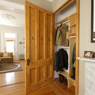 Eclectic gender-neutral medium tone wood floor reach-in closet photo in Providence