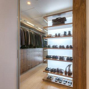 Foto di un'ampia cabina armadio unisex minimalista con ante lisce, ante in legno scuro e parquet chiaro