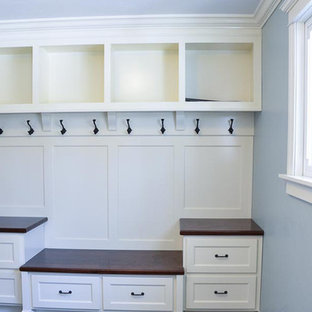 Example of a gender-neutral walk-in closet design in Other with shaker cabinets and white cabinets