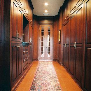 Foto di una grande cabina armadio unisex classica con ante con bugna sagomata, ante in legno bruno, pavimento in terracotta e pavimento marrone