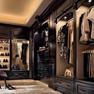 Foto de armario vestidor unisex, tradicional, extra grande, con puertas de armario de madera en tonos medios, suelo de baldosas de cerámica y armarios con paneles con relieve
