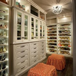 Modelo de armario y vestidor de mujer, clásico renovado, extra grande, con armarios con paneles empotrados, puertas de armario blancas y suelo de madera en tonos medios
