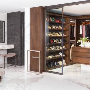 Modelo de armario vestidor de mujer, contemporáneo, con armarios con paneles lisos, puertas de armario de madera en tonos medios, suelo de mármol y suelo blanco