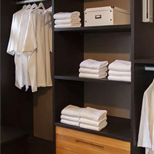 Diseño de armario vestidor unisex, actual, de tamaño medio, con armarios con paneles lisos, puertas de armario de madera oscura y suelo negro
