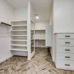 Foto de armario vestidor unisex, campestre, grande, con armarios con paneles lisos, puertas de armario blancas, suelo de baldosas de porcelana y suelo marrón