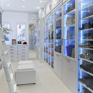 Trendy women's dressing room photo in Tampa with glass-front cabinets and white cabinets