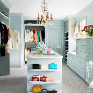 This is an example of a large traditional women's dressing room in Charlotte with recessed-panel cabinets, blue cabinets, carpet and grey floor.