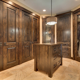 Photo of a large rustic gender neutral walk-in wardrobe in Portland with dark wood cabinets and travertine flooring.