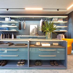 Modernes Ankleidezimmer mit Ankleidebereich, flächenbündigen Schrankfronten, blauen Schränken, Teppichboden und blauem Boden in Sonstige