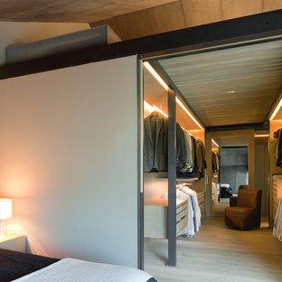 バルセロナの広い男女兼用コンテンポラリースタイルのおしゃれなウォークインクローゼット (フラットパネル扉のキャビネット、淡色木目調キャビネット、淡色無垢フローリング、ベージュの床) の写真