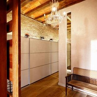 Cette photo montre un dressing tendance avec des portes de placard blanches et un sol en bois brun.