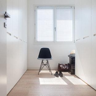 Diseño de vestidor unisex, contemporáneo, pequeño, con armarios con paneles lisos, puertas de armario blancas y suelo de madera clara
