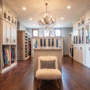 Modelo de vestidor unisex y abovedado, clásico renovado, grande, con armarios con paneles con relieve, puertas de armario grises, suelo de madera oscura y suelo marrón