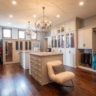 Exempel på ett stort klassiskt omklädningsrum för könsneutrala, med luckor med upphöjd panel, grå skåp, mörkt trägolv och brunt golv