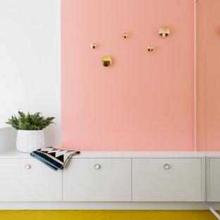 Diseño de armario vestidor unisex, actual, de tamaño medio, con armarios con paneles lisos, puertas de armario blancas, moqueta y suelo amarillo