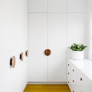 Cette image montre un dressing design de taille moyenne et neutre avec un placard à porte plane, des portes de placard blanches, moquette et un sol jaune.