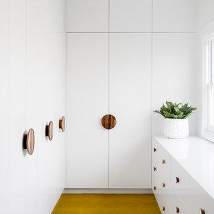 Modelo de armario vestidor unisex, actual, de tamaño medio, con armarios con paneles lisos, puertas de armario blancas, moqueta y suelo amarillo