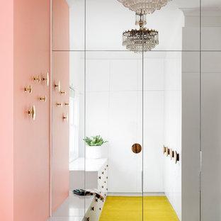 Immagine di una cabina armadio unisex contemporanea di medie dimensioni con ante lisce, ante bianche, moquette e pavimento giallo