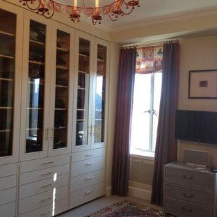Imagen de vestidor de mujer, bohemio, de tamaño medio, con armarios tipo vitrina, puertas de armario beige, moqueta y suelo beige