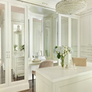 Inspiration for a large traditional women's dressing room in St Louis with recessed-panel cabinets, white cabinets, brown floor and dark hardwood floors.