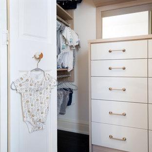 Ejemplo de armario vestidor unisex, campestre, pequeño, con armarios con paneles lisos, puertas de armario de madera oscura, suelo de madera pintada y suelo negro