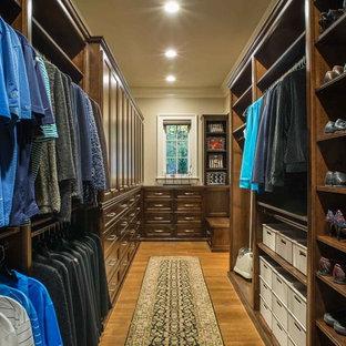 Ejemplo de armario vestidor unisex, clásico renovado, grande, con armarios con rebordes decorativos, puertas de armario de madera en tonos medios, suelo de madera oscura y suelo marrón