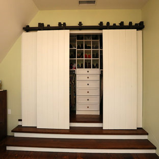 Example of a classic reach-in closet design in Santa Barbara with open cabinets and white cabinets