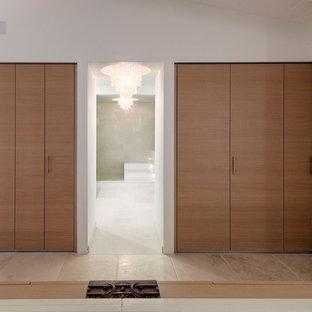 Großes Modernes Ankleidezimmer mit Ankleidebereich, flächenbündigen Schrankfronten, hellbraunen Holzschränken, Kalkstein und beigem Boden in San Luis Obispo