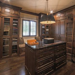 Diseño de vestidor de hombre, tradicional, extra grande, con armarios con paneles con relieve, puertas de armario de madera en tonos medios y suelo de madera oscura