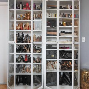 Idées déco pour un dressing et rangement classique pour une femme avec un placard à porte vitrée, des portes de placard blanches et un sol en bois brun.