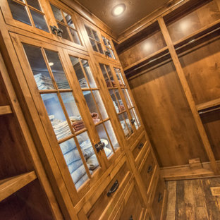 Design ideas for a mid-sized country gender-neutral walk-in wardrobe in Other with recessed-panel cabinets, medium wood cabinets and dark hardwood floors.