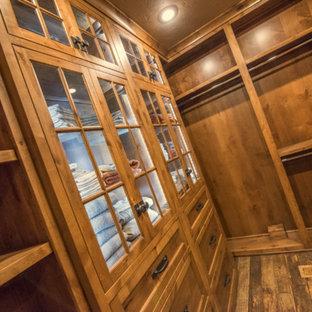 Diseño de armario vestidor unisex, rústico, de tamaño medio, con armarios con paneles empotrados, puertas de armario de madera oscura y suelo de madera oscura
