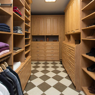 Immagine di una grande cabina armadio unisex american style con ante con bugna sagomata, ante in legno chiaro, pavimento in gres porcellanato e pavimento multicolore