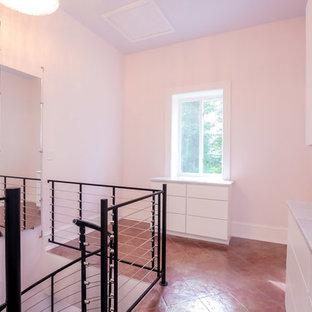 Diseño de armario vestidor de mujer, industrial, con armarios con paneles lisos, puertas de armario blancas y suelo de baldosas de terracota