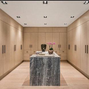 Foto di uno spazio per vestirsi unisex design con ante lisce, ante in legno chiaro, parquet chiaro e pavimento beige