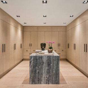ニューヨークの広い男女兼用コンテンポラリースタイルのおしゃれなウォークインクローゼット (フラットパネル扉のキャビネット、淡色木目調キャビネット、淡色無垢フローリング、ベージュの床) の写真