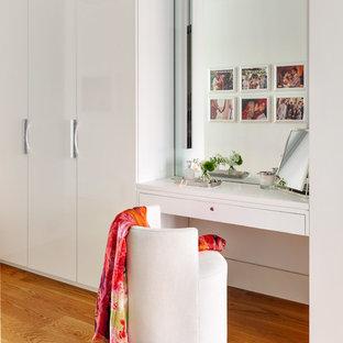 Cette photo montre un dressing room scandinave pour une femme avec un placard à porte plane, des portes de placard blanches et un sol en bois brun.