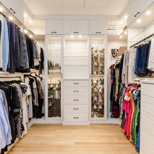 Cette image montre un très grand dressing design neutre avec un sol en bois clair et des portes de placard en bois clair.