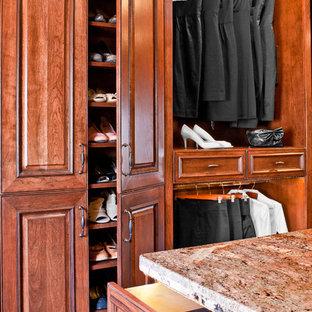 Modelo de armario vestidor de mujer, tradicional, grande, con armarios con paneles con relieve, puertas de armario de madera oscura y suelo de madera en tonos medios
