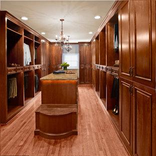 Ispirazione per una grande cabina armadio unisex chic con ante con bugna sagomata, ante in legno bruno e pavimento in legno massello medio