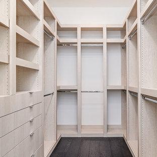Imagen de armario vestidor de hombre, actual, grande, con armarios con paneles con relieve, puertas de armario beige y suelo de madera oscura