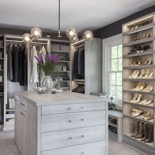 Design ideas for a large transitional gender-neutral dressing room in New York with flat-panel cabinets, distressed cabinets and carpet.