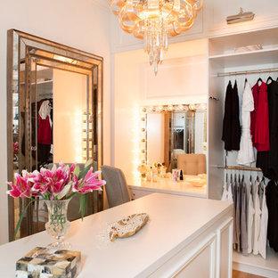 Idéer för att renovera ett stort medelhavsstil walk-in-closet för kvinnor, med vita skåp, ljust trägolv och luckor med upphöjd panel