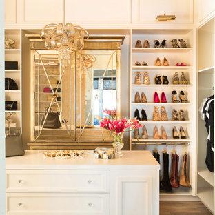 Modelo de armario vestidor de mujer, tradicional renovado, grande, con puertas de armario blancas, suelo de madera clara y armarios con paneles empotrados