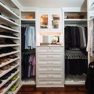 Diseño de armario vestidor de mujer, clásico renovado, pequeño, con armarios con rebordes decorativos, puertas de armario blancas, suelo de madera oscura y suelo marrón