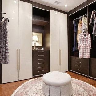 シカゴの大きい女性用コンテンポラリースタイルのおしゃれなフィッティングルーム (フラットパネル扉のキャビネット、茶色いキャビネット、竹フローリング) の写真