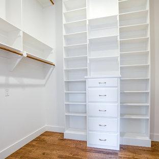 Exempel på ett stort lantligt walk-in-closet för könsneutrala, med luckor med lamellpanel, vita skåp, mellanmörkt trägolv och brunt golv