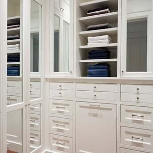 Country gender-neutral walk-in wardrobe in Richmond with white cabinets and medium hardwood floors.
