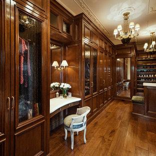Modelo de vestidor mediterráneo con armarios con paneles empotrados y puertas de armario de madera en tonos medios