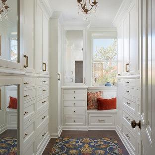 Imagen de vestidor unisex, tradicional, con puertas de armario blancas, suelo de madera oscura y suelo marrón